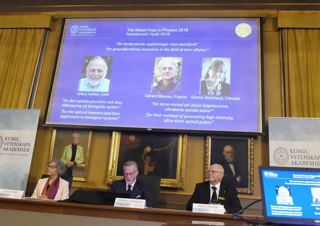 Members of the Nobel Committee for Physics (L-R) Olga Botner, Goran K Hansson and Mats Larsson sit in front of a screen displaying portraits of Arthur Ashkin of the United States, Gerard Mourou of France and Donna Strickland of Canada during the announcement of the winners of the 2018 Nobel Prize in Physics.