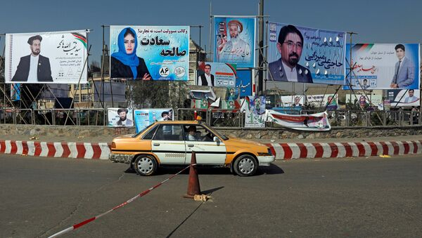 A vehicle drives in front of election posters of parliamentarian candidates installed during the first day of elections campaign in Kabul, Afghanistan September 28, 2018 - Sputnik International
