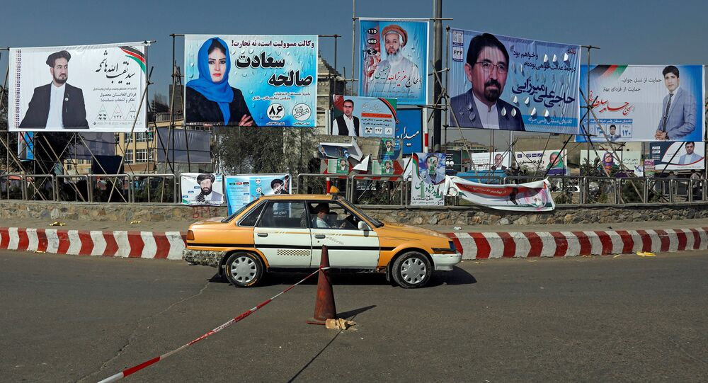 A vehicle drives in front of election posters of parliamentarian candidates installed during the first day of elections campaign in Kabul, Afghanistan September 28, 2018