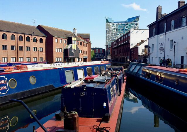 Canal boats remain moored at the Gas Street Basin in Birmingham, UK.
