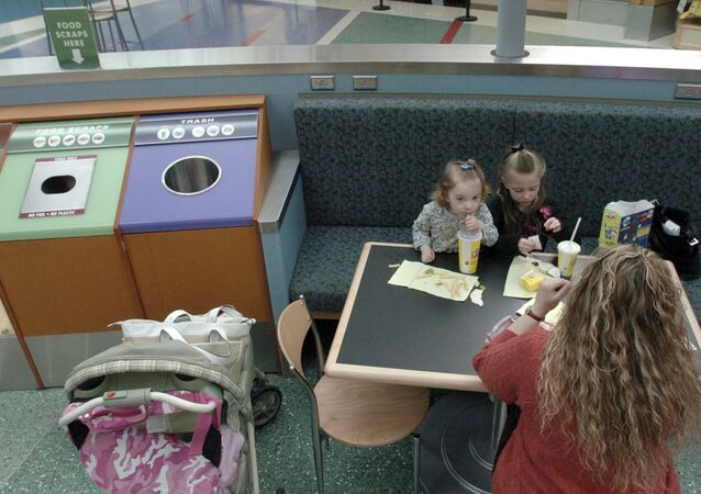 Lena Miller, right, with her daughters Kennedi, 2, left, and Kelsea Miller, 6, eat their lunch next to a new specially labeled bin containing a biodegradable bag at an eating area on the departure concourse at Portland International Airport in Portland, Ore., Thursday Nov.20, 2008. The airport is ramping up a three-year-old program to install food-only trash cans. The food waste is collected in biodegradable bags and given to the city to use as compost, said Stan Jones, aviation environmental compliance manager at the airport.