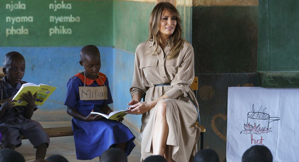 First lady Melania Trump helps a student as she visits a language class at Chipala Primary School, in Lilongwe, Malawi, Thursday, Oct. 4, 2018. Mrs. Trump is visiting Africa on her first big solo international trip, aiming to make child well-being the focus of a five-day, four-country tour.