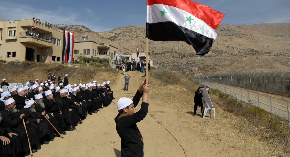 Druze people take part in a rally in Majdal Shams near the ceasefire line between Israel and Syria in the Israeli occupied Golan Heights