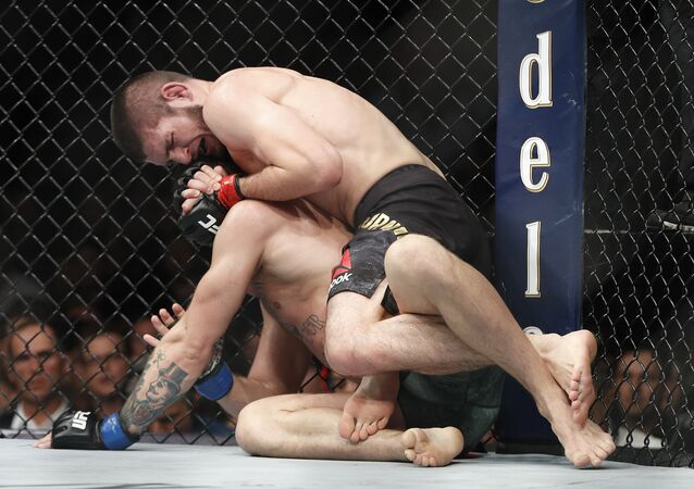 Khabib Nurmagomedov, top, applies a rear naked choke hold to Conor McGregor during a lightweight title mixed martial arts bout at UFC 229 in Las Vegas, Saturday, Oct. 6, 2018