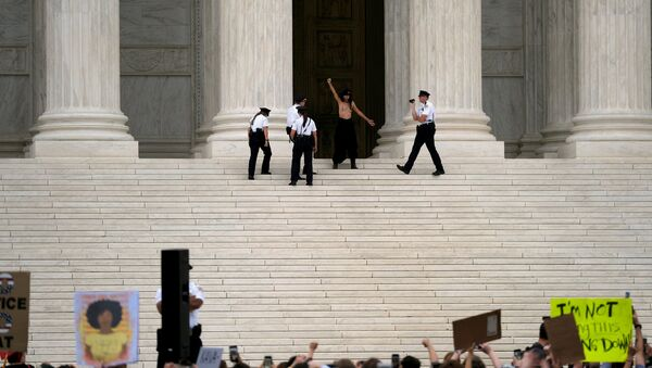 A topless woman is detained by Supreme Court Police after the Senate confirmed the nomination of Judge Brett Kavanaugh in Washington, U.S., October 6, 2018 - Sputnik International