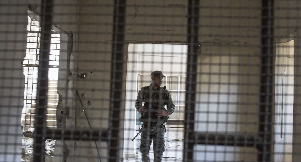 A member of the U.S.-backed Syrian Democratic Forces (SDF) walk inside a prison built by Islamic State fighters at the stadium that was the site of IS fighters' last stand in the city of Raqqa, Syria, Friday, Oct. 20, 2017