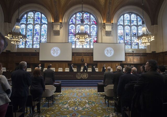 In this Wednesday Oct. 3, 2018, image The delegations of the U.S., front left, and the Islamic Republic of Iran, front right, rise as judges, rear, enter the International Court of Justice, or World Court, in The Hague, Netherlands