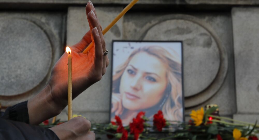 A woman holds a candle next to a portrait of slain television reporter Viktoria Marinova during a vigil at the Liberty Monument in Ruse, Bulgaria, Monday, Oct. 8, 2018.