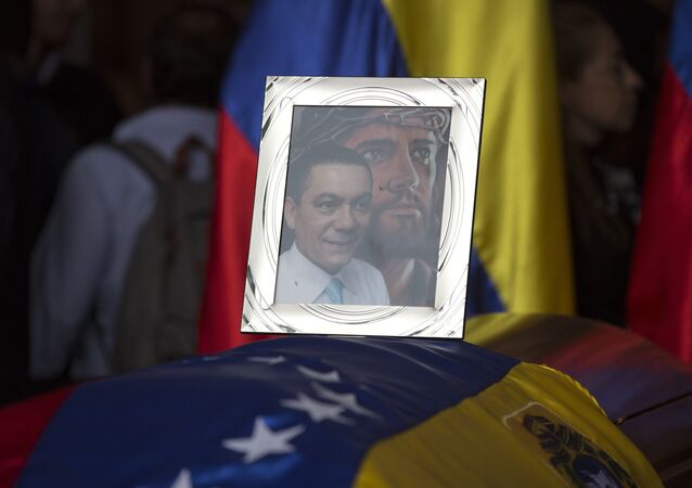 A framed portrait of opposition activist Fernando Alban shadowed by an image of Jesus Christ sits on the flag-draped casket containing his remains, during a solemn ceremony at the National Assembly headquarters, in Caracas, Venezuela, Tuesday, Oct. 9, 2018