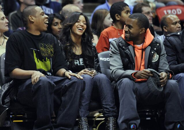 Entertainers Jay-Z, left, Beyonce and Kanye West, right, laugh during the New Jersey Nets' NBA basketball game against the Seattle SuperSonics on Wednesday night, Jan. 9, 2008, in East Rutherford, N.J.