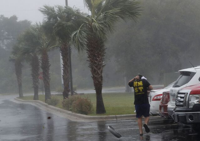 A hubcap blows by as a man runs to his car during Hurricane Michael in Panama City, Fla., Wednesday, Oct. 10, 2018.