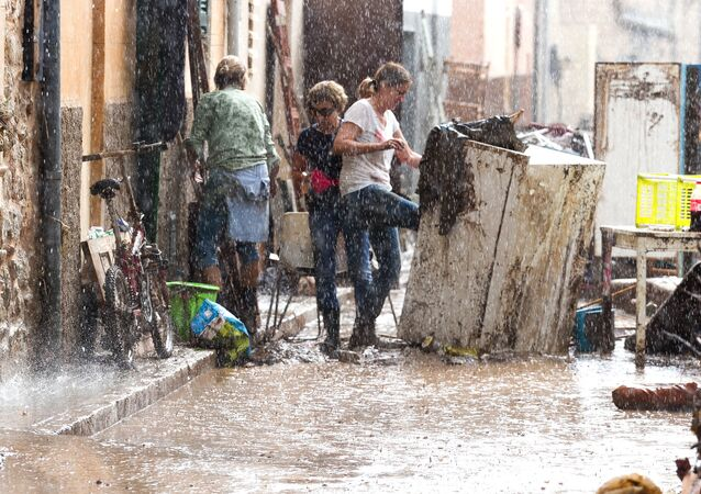 Residents place their damaged belongings on the street under pouring rain, in Sant Llorenc, 60 kilometers (40 miles) east of Mallorca's capital, Palma, Spain, Wednesday, Oct. 10, 2018.