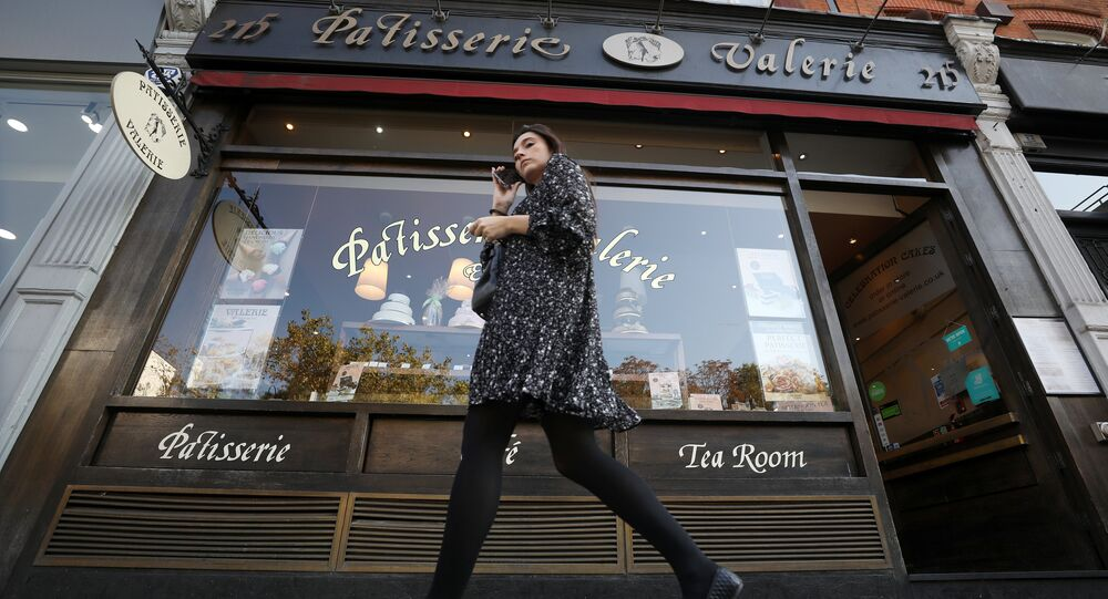 A woman walks past a branch of Patisserie Valerie in London