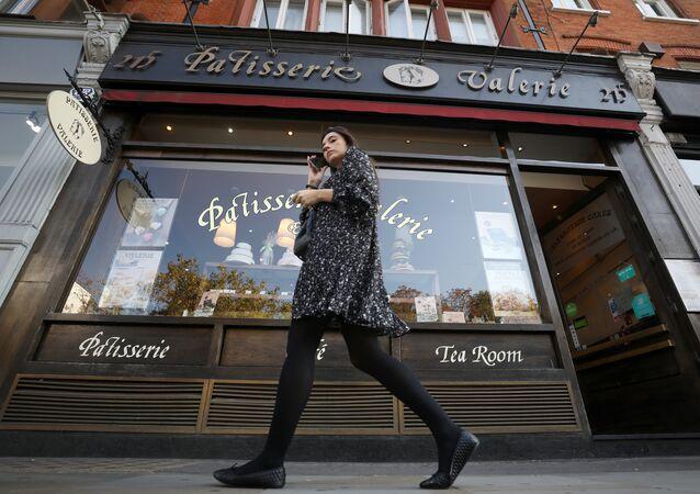A woman walks past a branch of Patisserie Valerie in London