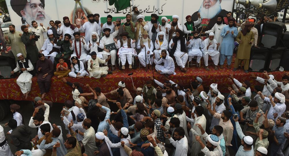 Supporters of Tehreek-e-Labaik Pakistan (TLP), a hardline religious political party, surround their party leader Khadim Hussain Rizvi (C top) during a protest rally in Lahore on October 12, 2018 demanding for hanging to a blasphemy convict Christian woman Asia Bibi, who is on death row.
