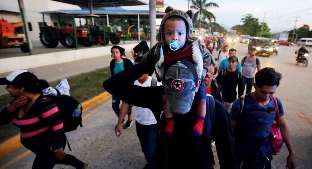 A man carries a child along other Hondurans fleeing poverty and violence, as they move in a caravan toward the United States, in San Pedro Sula, Honduras October 13, 2018