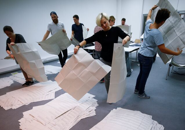 Electoral officials sort ballot papers after the conclusion of voting in the Bavarian state election in Munich, Germany