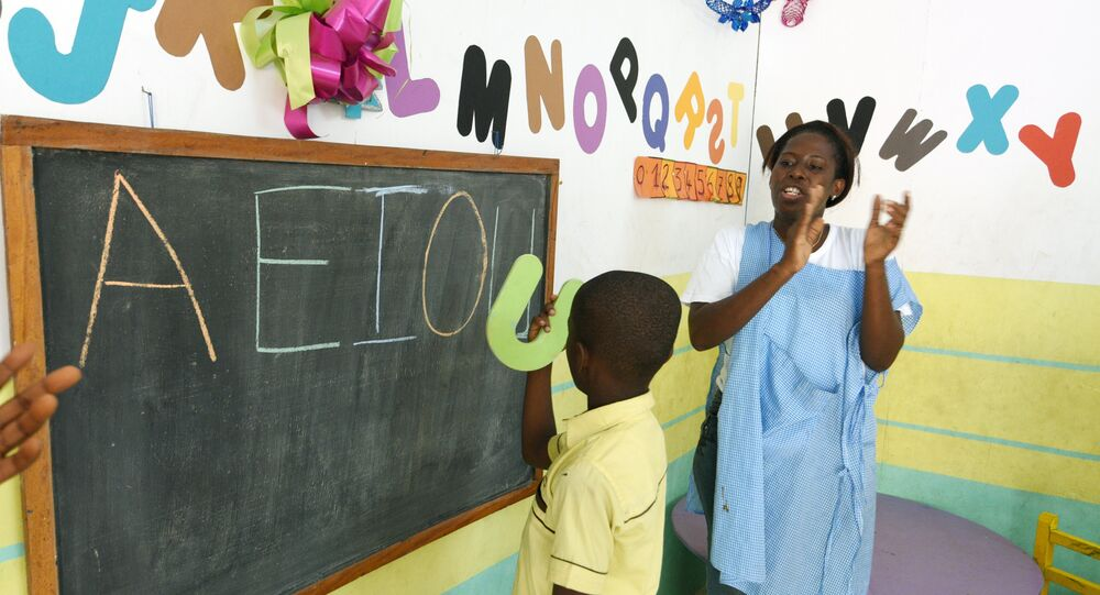 A teacher applauds an autistic child in classroom in Abidjan, Ivory Coast. Autism is less likely to be diagnosed in the developing world