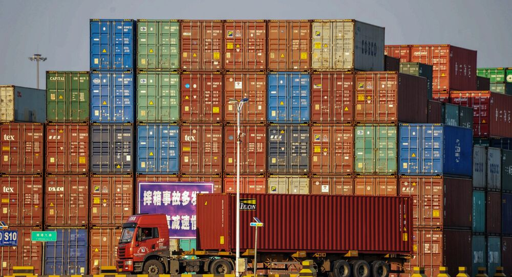A truck transports a container next to stacked containers at a port in Qingdao in China's eastern Shandong province on October 12, 2018
