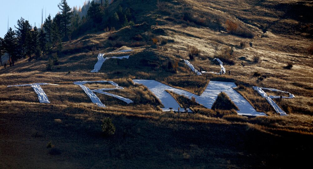 Activist use fabric to spell out a temporary message around the concrete M above the University of Montana ahead of U.S. President Donald Trump's arrival to Missoula.