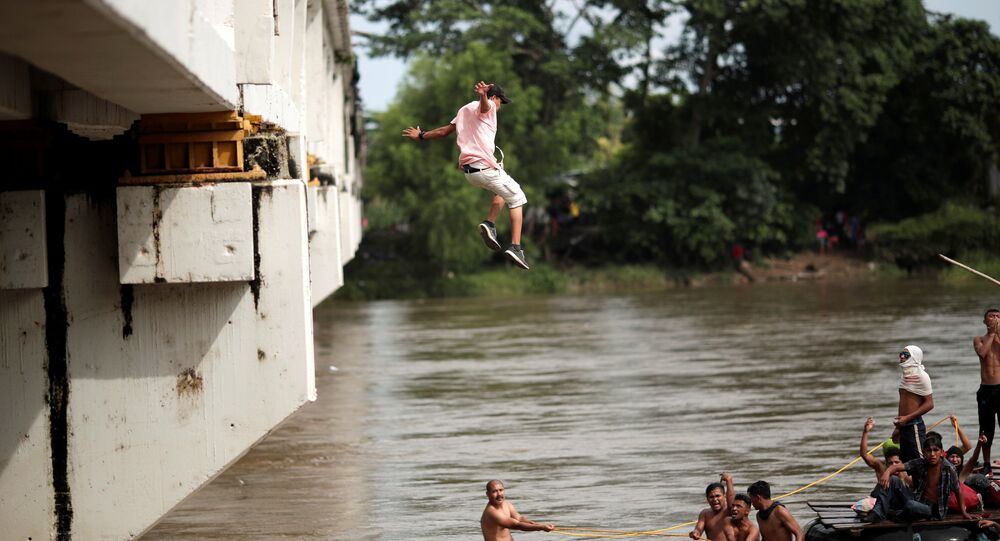 A Honduran migrant jumps from the bridge that connects Mexico and Guatemala to avoid the border checkpoint in Ciudad Hidalgo