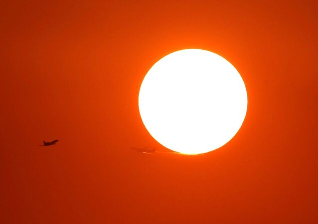 Two planes fly in front of the setting sun in Shanghai, China October 2, 2018