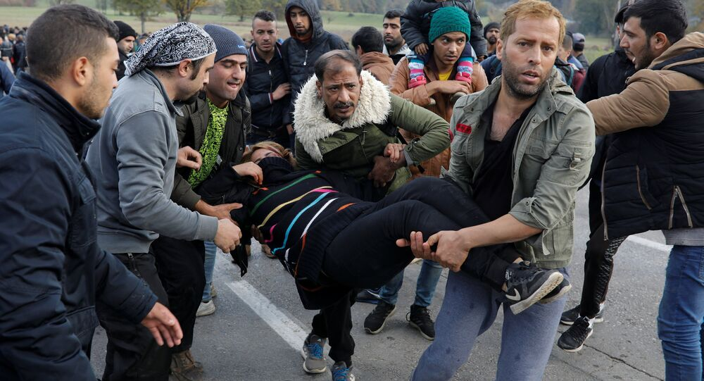 Migrants carry a woman who was injured during minor clashes with Croatian riot police at Maljevac border crossing between Bosnia and Croatia near Velika Kladusa, Bosnia, October 24, 2018