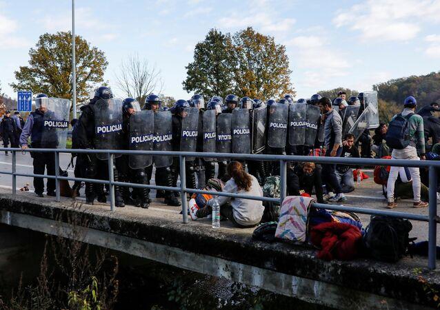 Croatian riot police stand guard in front of migrants at Maljevac border crossing between Bosnia and Croatia near Velika Kladusa, Bosnia, October 24, 2018