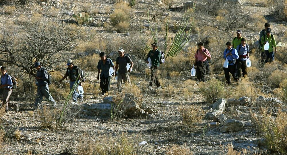 Mexican immigrants walk in line through the Arizona desert near Sasabe, Sonora state, in an attempt to illegally cross the Mexican-US border