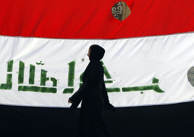 An Iraqi woman walks her national flag