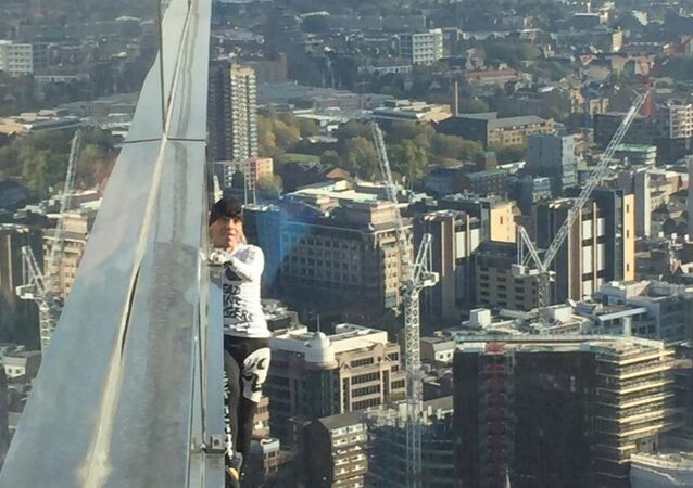 Alain Robert, known as 'Spiderman', climbs the Heron Tower in London