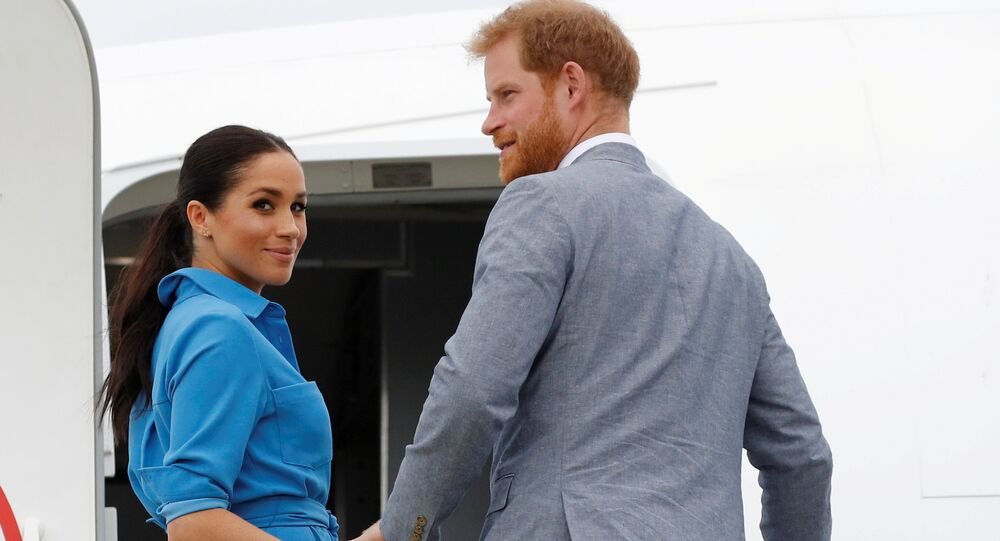 Britain's Prince Harry and Meghan, Duchess of Sussex look on before departing from Fua'amotu International Airport in Tonga October 26, 2018.