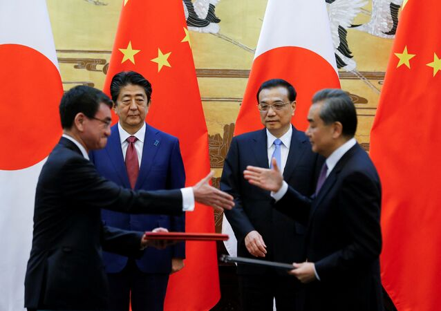 Chinese Premier Li Keqiang, Japanese Prime Minister Shinzo Abe, Chinese Foreign Minister Wang Yi and Japanese Foreign Minister Taro Kono attend a signing ceremony in Beijing