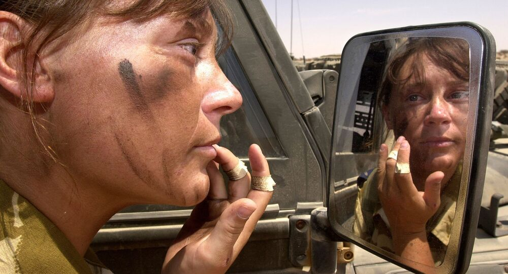 Senior Aircrafts Women Chantelle Robins, 21, from Yelverton, based with First Squadron Royal Air force Regiment at RAF St. Mawgan, UK, puts on combat make-up in Oman 29 September 2001
