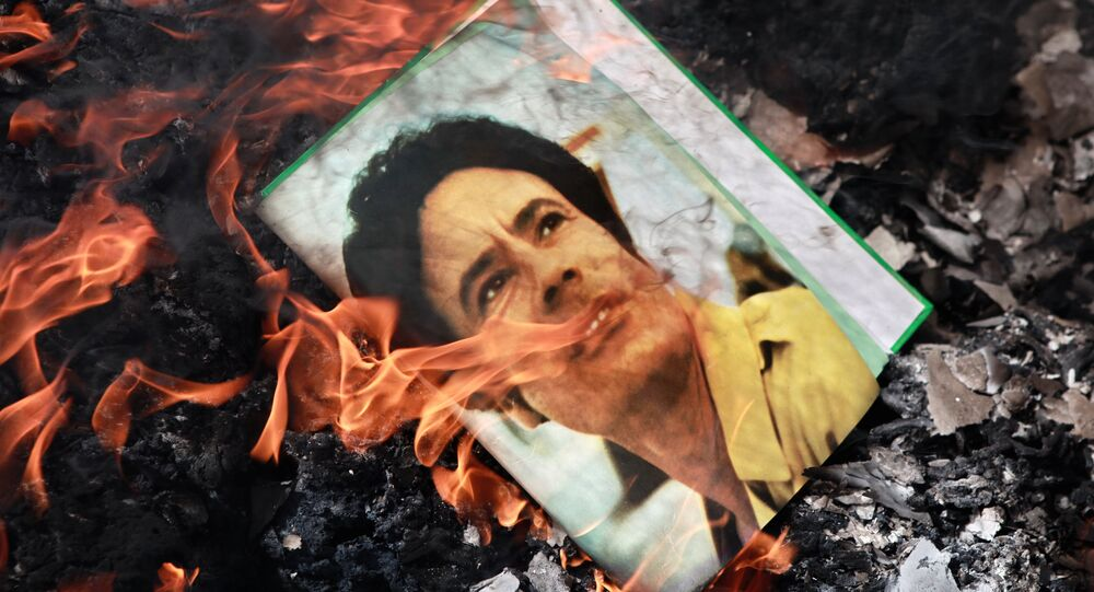 A portrait of Muammar Gaddafi burning in a fire.