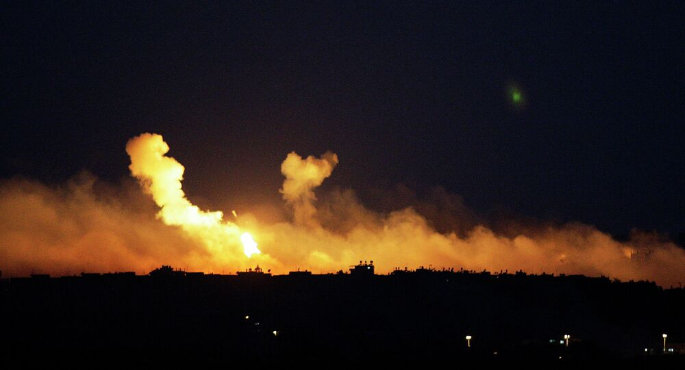 The sky is illuminated by explosions from Israeli military operations over the outskirts of Gaza City