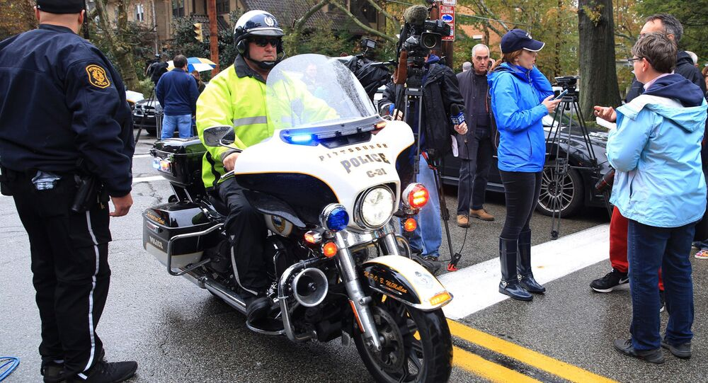 A police officer on motorcycle passes through a roadblock as he responds after a gunman opened fire at the Tree of Life synagogue in Pittsburgh.