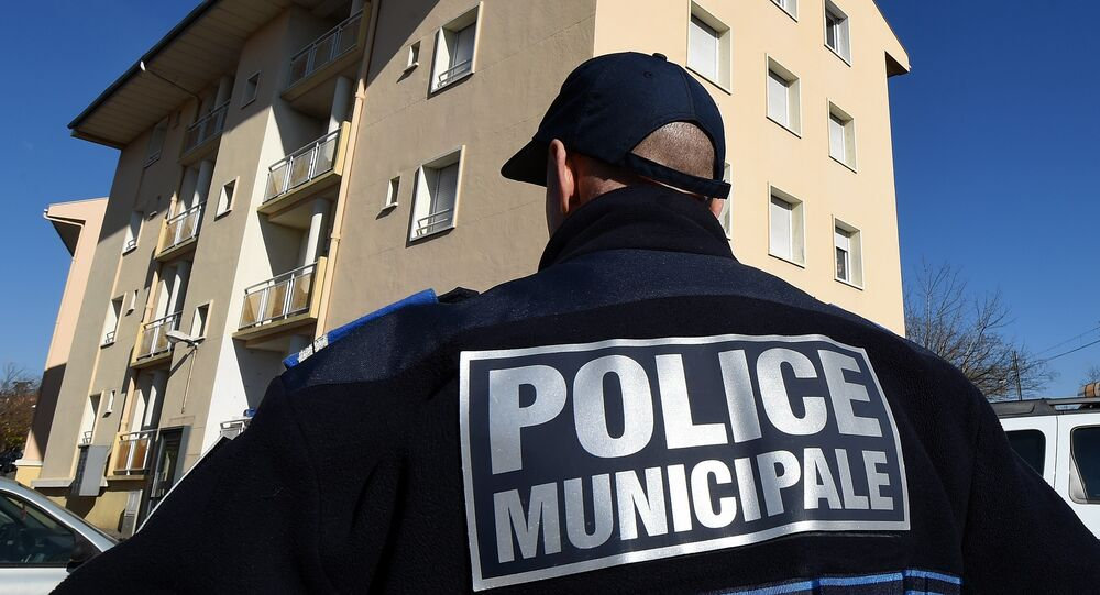 A municipal police officer stands January 22, 2015 in front of a building in Beziers, southern France, where a Russian Chechen suspected of preparing a terrorist attack was living before his January 19 arrest