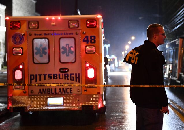 An FBI agent stands behind a police cordon and an ambulance outside the Tree of Life Synagogue (L) after a shooting there left 11 people dead in the Squirrel Hill neighborhood of Pittsburgh on October 27, 2018.