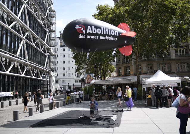 A woman sits underneath a balloon shaped like a nuclear bomb outside the Centre Georges Pompidou in Paris on August 7, 2017, during an action and four-day hunger strike organised by the network Sortir du nucleaire and the collective Abolition des armes nucleaires - Maison de Vigilance to call for the disarmament of nuclear weapons and for France to sign a UN treaty to ban nuclear weapons