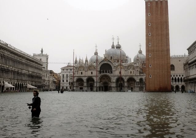 A man walks in the flooded St. Mark's Square during a high-water (Acqua Alta) alert in Venice on October 29, 2018 The flooding, caused by a convergence of high tides and a strong Sirocco wind, reached around 150 centimetres on October 29.
