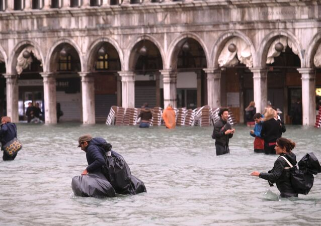 People walk in a flooded Saint Mark Square during a period of seasonal high water in Venice, Italy October 29, 2018