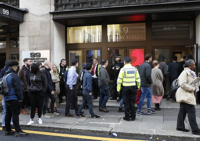 Police officers and security watch as people re-enter a building after a stabbing incident in central London, Friday, Nov. 2, 2018