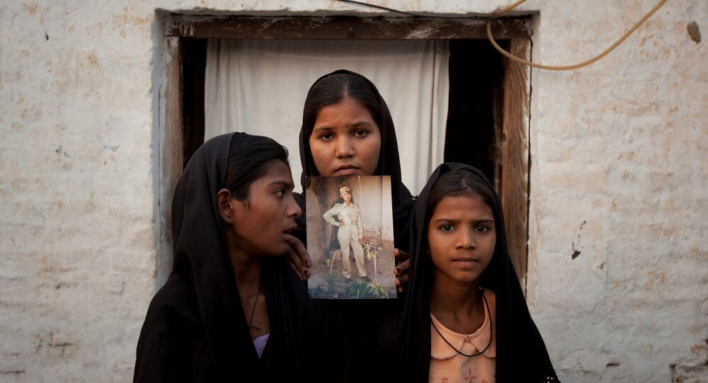 The daughters of Pakistani Christian woman Asia Bibi pose with an image of their mother while standing outside their residence in Sheikhupura located in Pakistan's Punjab Province (File)