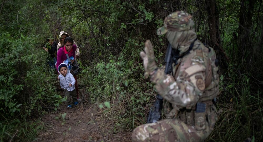 A member of the U.S. Border Patrol Tactical Unit (BORTAC) acknowledges family members after they illegally crossed the Rio Grande river into the United States from Mexico in Fronton, Texas, October 18, 2018
