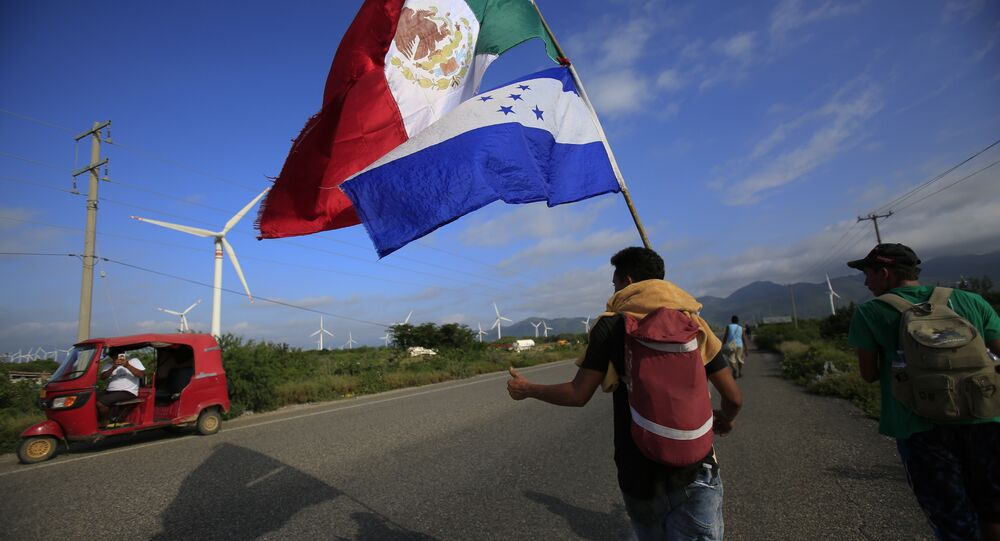 A migrant carrying the flags of Mexico and Honduras gives a thumbs-up to a moto rickshaw driver who stopped to take their picture, as a thousands-strong caravan of Central Americans hoping to reach the U.S. border moves onward from Juchitan, Oaxaca state, Mexico, Thursday, Nov. 1, 2018. Thousands of migrants resumed their slow trek through southern Mexico on Thursday, after attempts to obtain bus transport to Mexico City failed