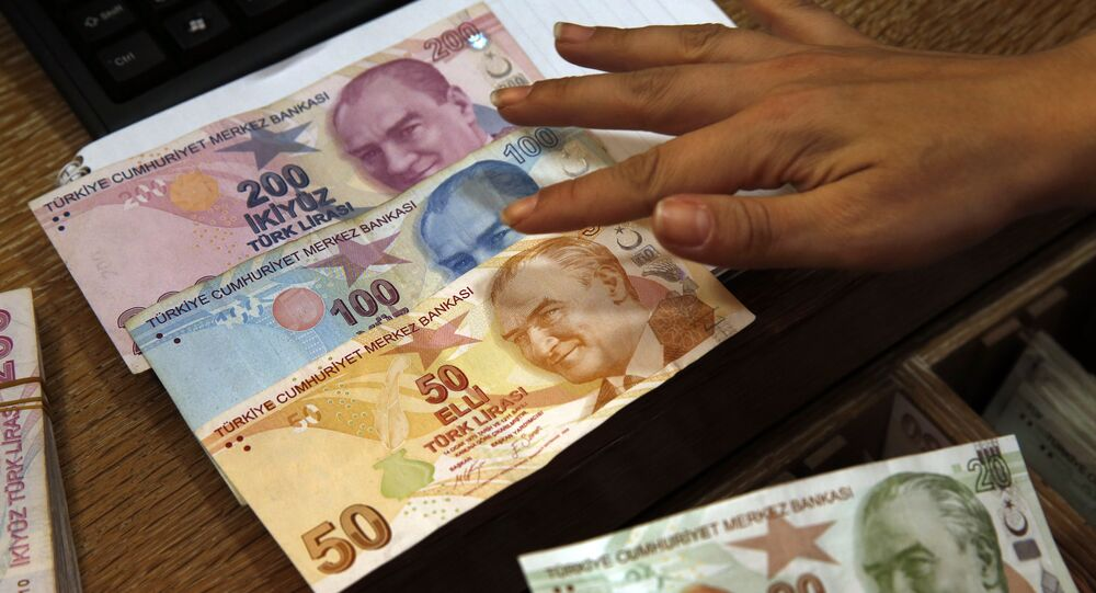 In this Wednesday, Aug. 15, 2018, file photo a worker at a currency exchange shop exhibits Turkish lira banknotes bearing pictures of modern Turkey's founder Mustafa Kemal Ataturk, in Istanbul.(file photo)