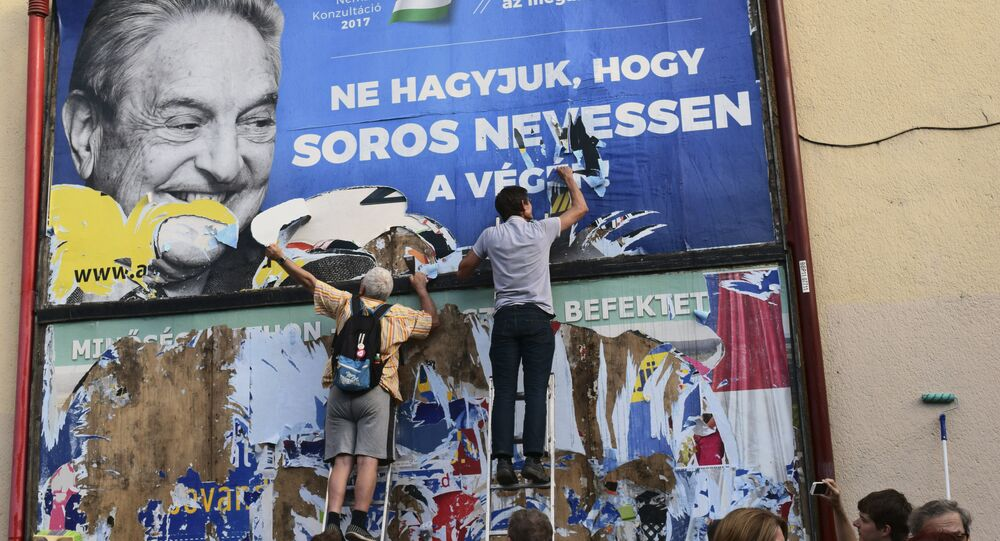 activists of the Egyutt (Together) party tear down an ad by the Hungarian government against George Soros, in Budapest, Hungary