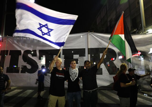 Arab Israelis and their supporters carry a Palestinian (R) and an Israeli flag during a demonstration
