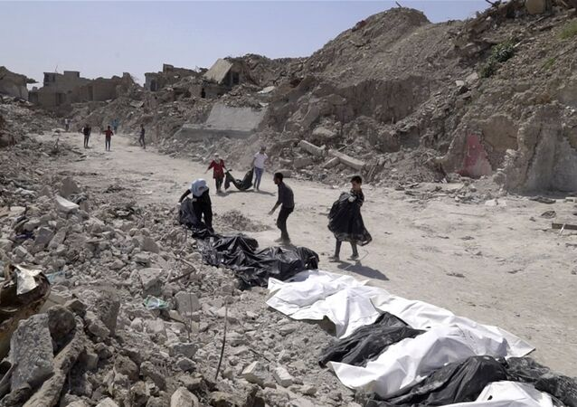 In this image made from video taken on Monday, April 9, 2018, bodies are recovered by volunteers in Mosul's Old City